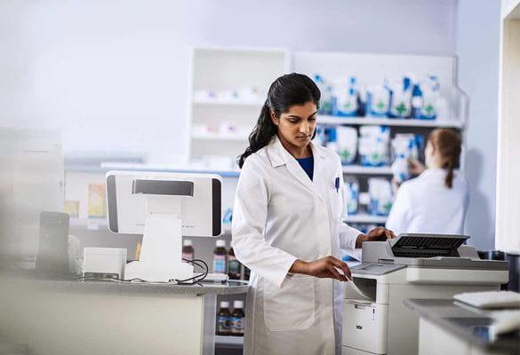 Pharmacist using a printer