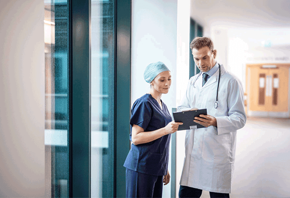 a doctor and a nurse looking at a clipboard
