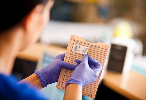 Female healthcare professional applying a printed identification label to patient records at a hospital ward reception desk