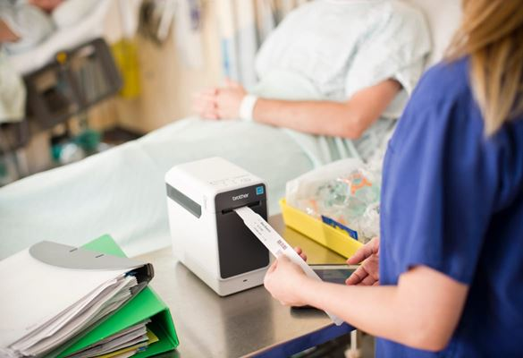 Healthcare professional removing an identification wristband from a label printer with a patient sat upright in a hospital bed in the background
