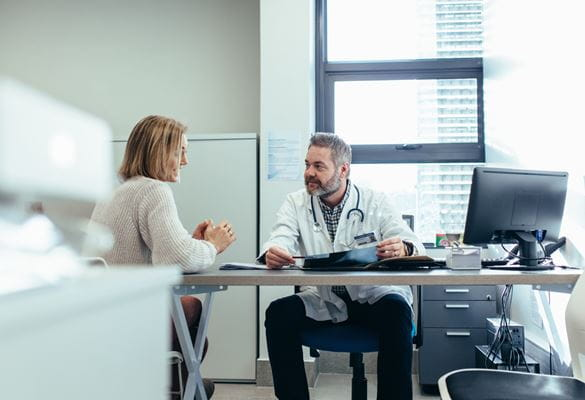 Doctor and patient chatting in doctors surgery