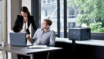 Businessman and businesswoman looking at a document in a office