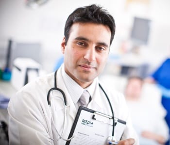 Doctor on a ward with a stethoscope around his neck holding a chart with a patient in a bed in the background