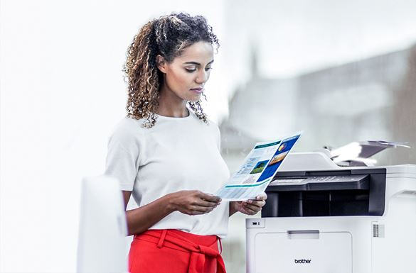 A woman reviewing a printed piece of paper whilst standing next to a Brother printer