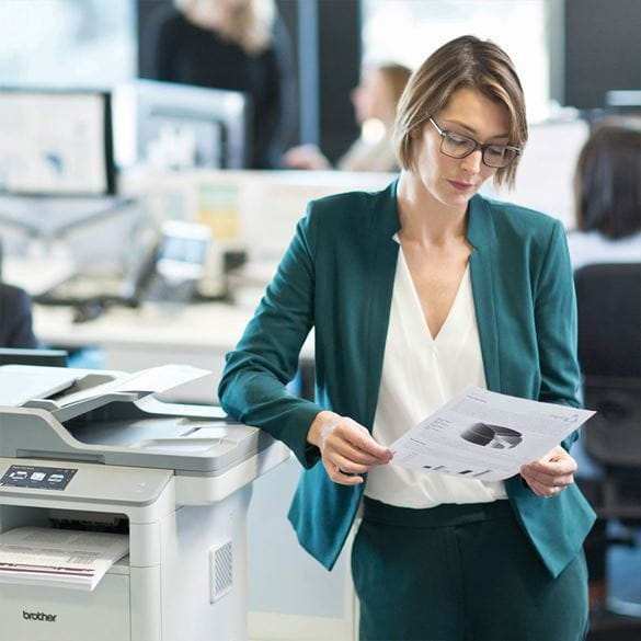 A woman in a teal suit standing next to a Brother printer and reviewing some printed paper