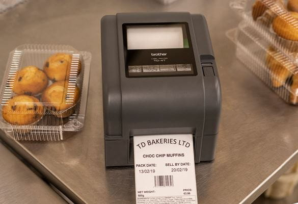 Grey Brother label printer with printed label in machine, next to clear plastic chocolate muffin boxes on stainless steel bench