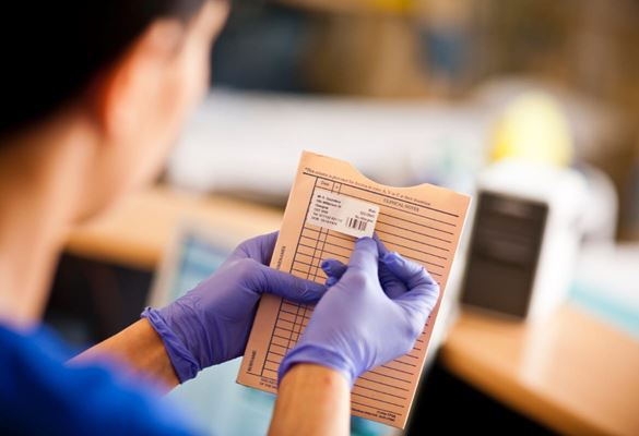Medical professional wearing purple gloves applying printed label to patients clinical notes