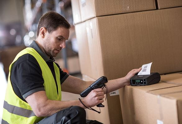 Man wearing hi-vis holding scanner printing label, label printer on top of boxes in warehouse