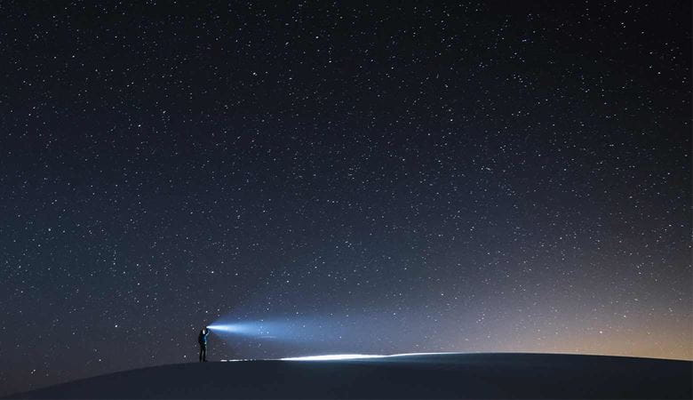 night time sky with stars and a man shining a torch