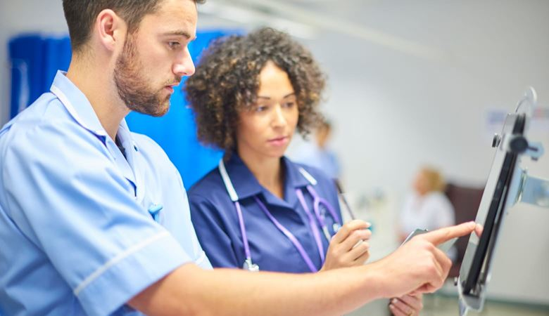 Male nurse checking information on a tablet device while being supervised by a female staff nurse