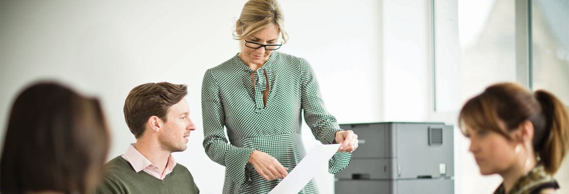 Woman standing talking to a man sitting at a desk