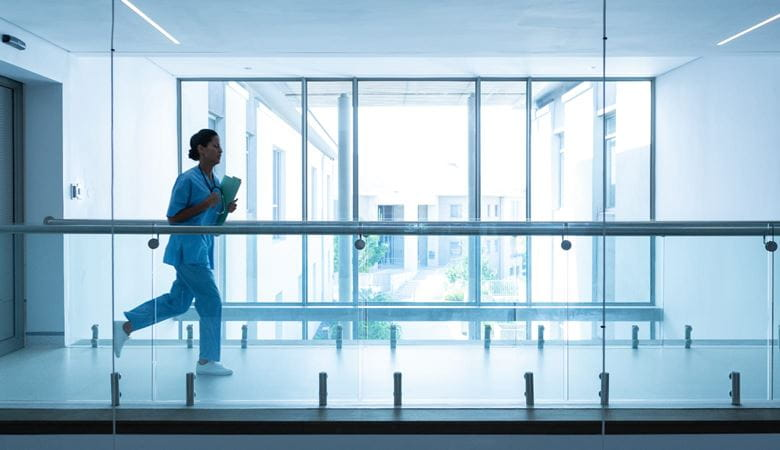Female surgeon carrying medical reports running along a corridor in a hospital