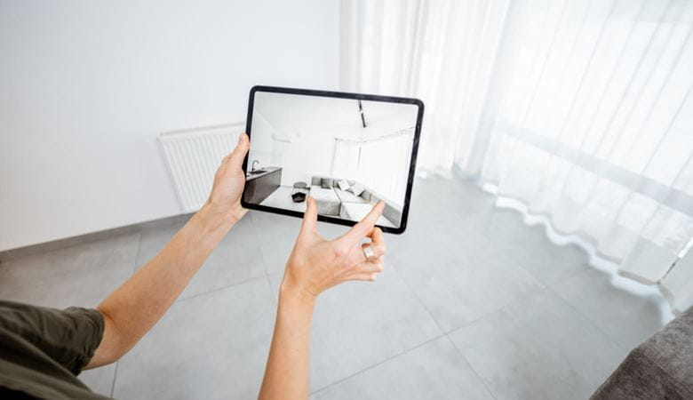 A person in an empty room using an augmented reality app on a tablet device to make interior design decisions