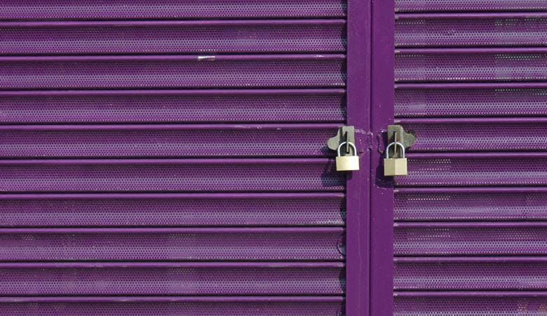 Two padlocks on purple retail store shutters