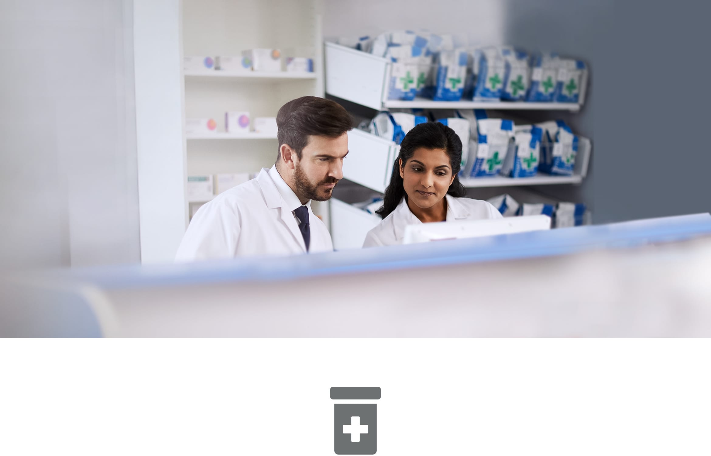 Male and Female pharmacists behind counter in pharmacy