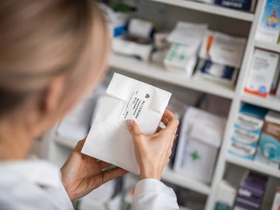 Pharmacist applying a printed label to a prescription in the pharmacy department of Medway NHS Foundation Trust