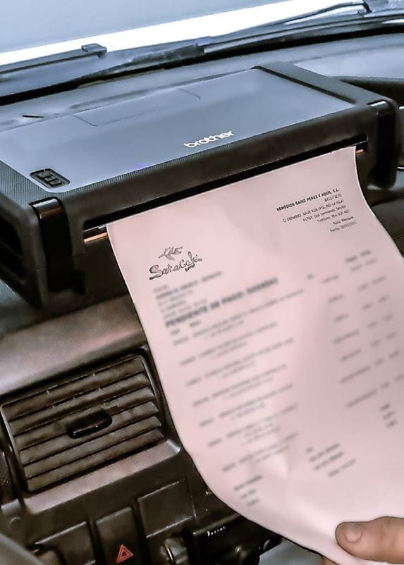 Sales person printing an invoice on a Brother PJ-762 mobile printer, installed on the dashboard of a Soto Café field sales vehicle