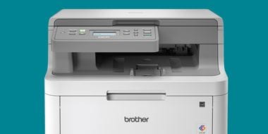 A grey Brother colour laser printer on a teal background