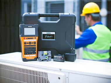 Brother PT-E550 labeller with supplies and accessories on a commercial air conditioning unit outside a building with an electrician wearing a hard hat and high visibility vest in the background
