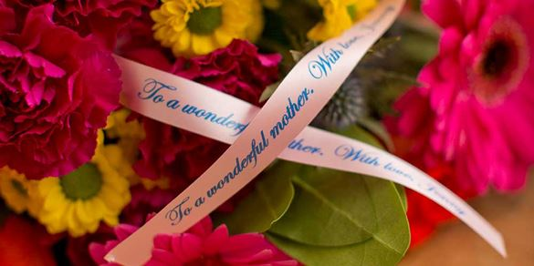 A pink personalised ribbon on a bouquet of flowers created on the Brother Tape Creator