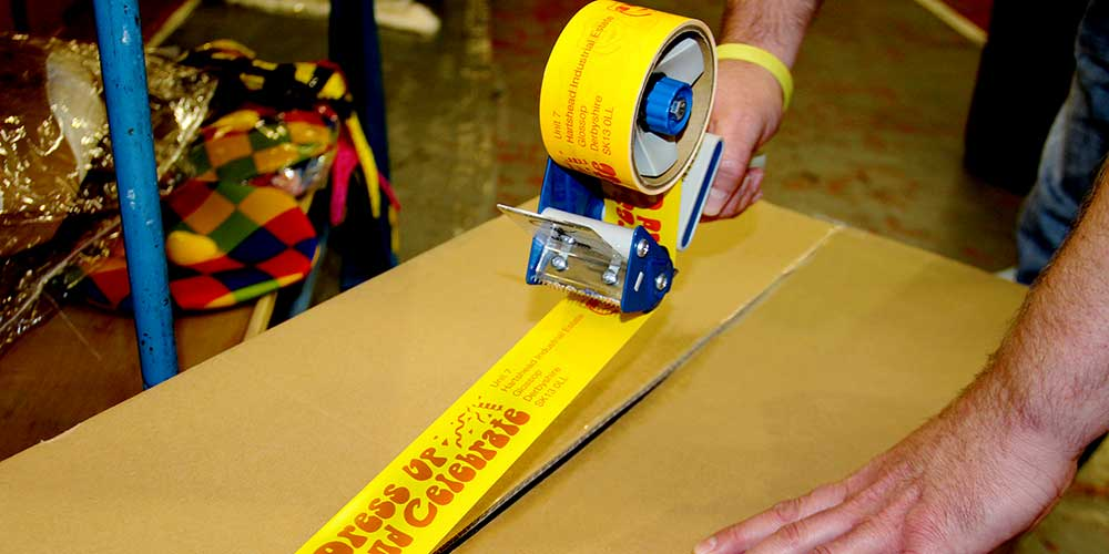 A warehouse worker seals a box shut with customised packing tape created on the Brother Tape Creator Pro