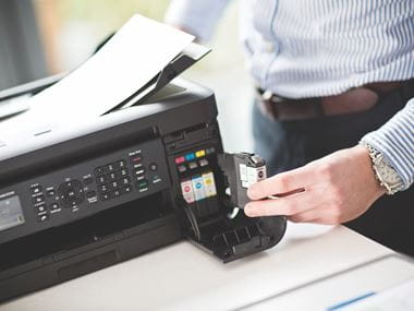 A man changing an ink cartridge in a Brother inkjet printer