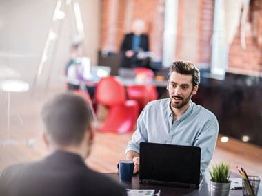 A supplier discussing a service level agreement with a customer across a desk in an office environment