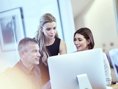 Three colleagues chatting in an office environment