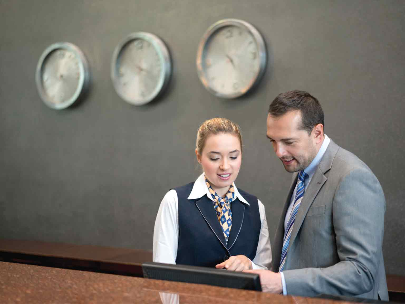 Two hotel receptionists looking at a computer screen