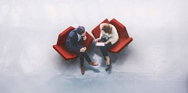 Overhead view of two business people looking at information on a tablet device while sitting on red chairs in a lobby