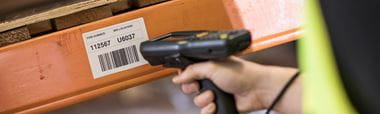 Warehouse racking with Brother thermal label containing a barcode, being scanned with barcode scanner.