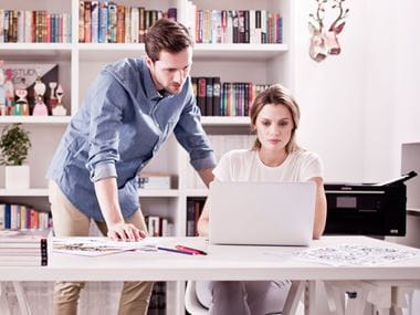 En kvinne sitter ved et skvrivebord med en laptop, en mann står ved siden av