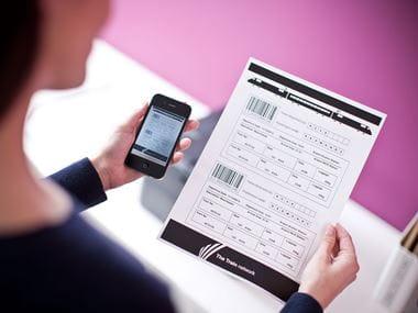 En kvinne holder en mobil og et utskrevet dokument i hendene