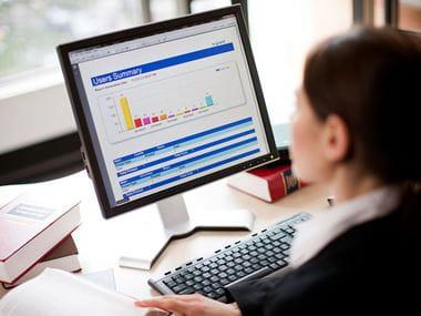 En kvinne ser på en dataskjerm med grafer