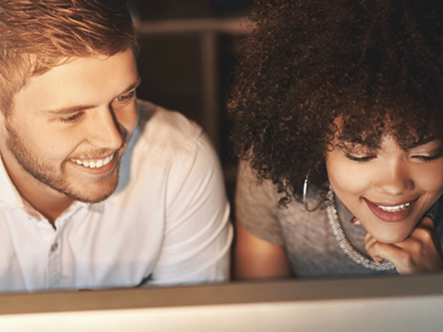 Man and woman smiling while looking at something out of shot