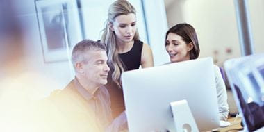 Three colleagues looking at a computer monitor in an office environment