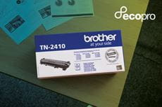 Brother toner cartridge carton on tabletop alongside black and white printed documents