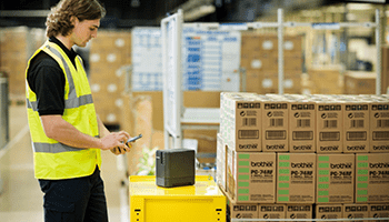 Man wearing a high visibility vest in a warehouse printing a label from a smartphone
