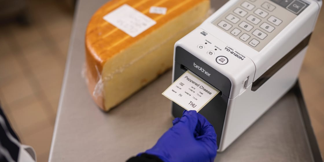 A person out of shot wearing a blue latex glove removing a food label from a Brother TD-2120N industrial label printer, next to a block of cheese in a commercial kitchen environment