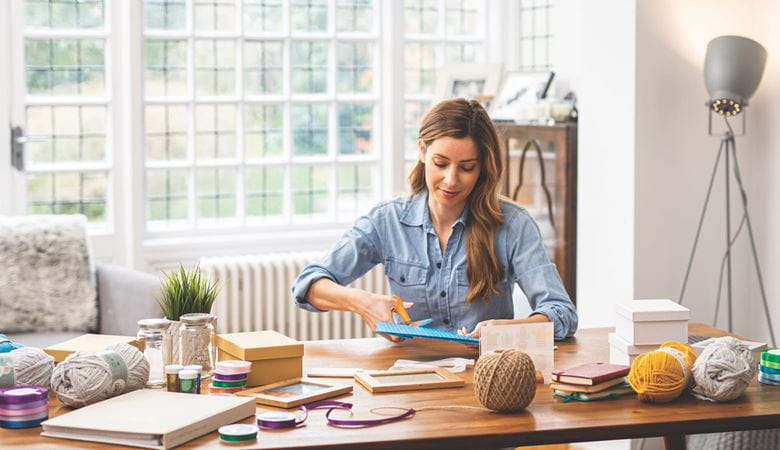 Woman sat at home office desk using arts and crafts