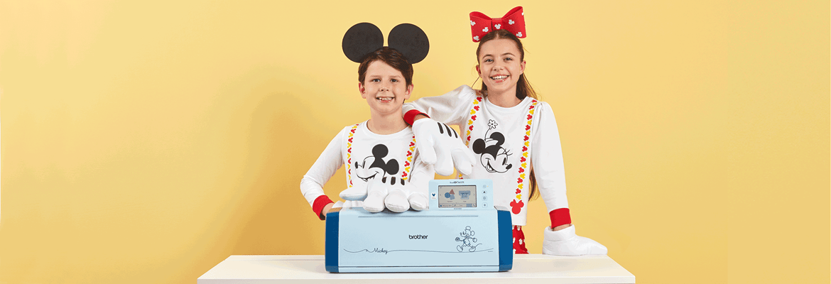 Boy and girl in Mickey outfits with SDX2250D on yellow background