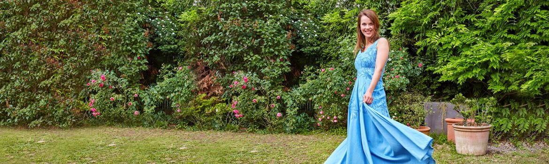 Девушка в синем вышитом платье в саду