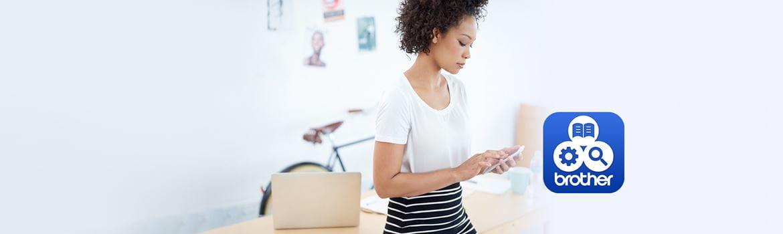 Женщина с помощью своего смартфона в домашнем офисе