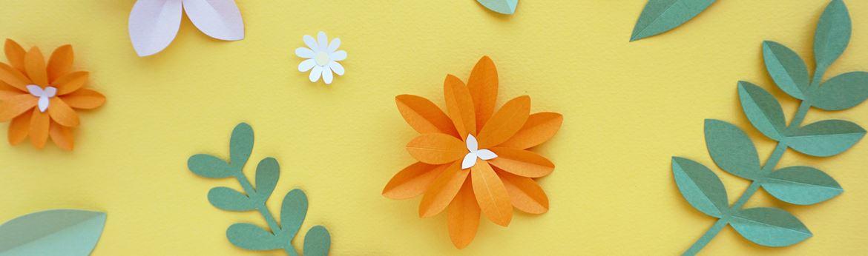 Вырезанные из бумаги цветы на желтом фоне