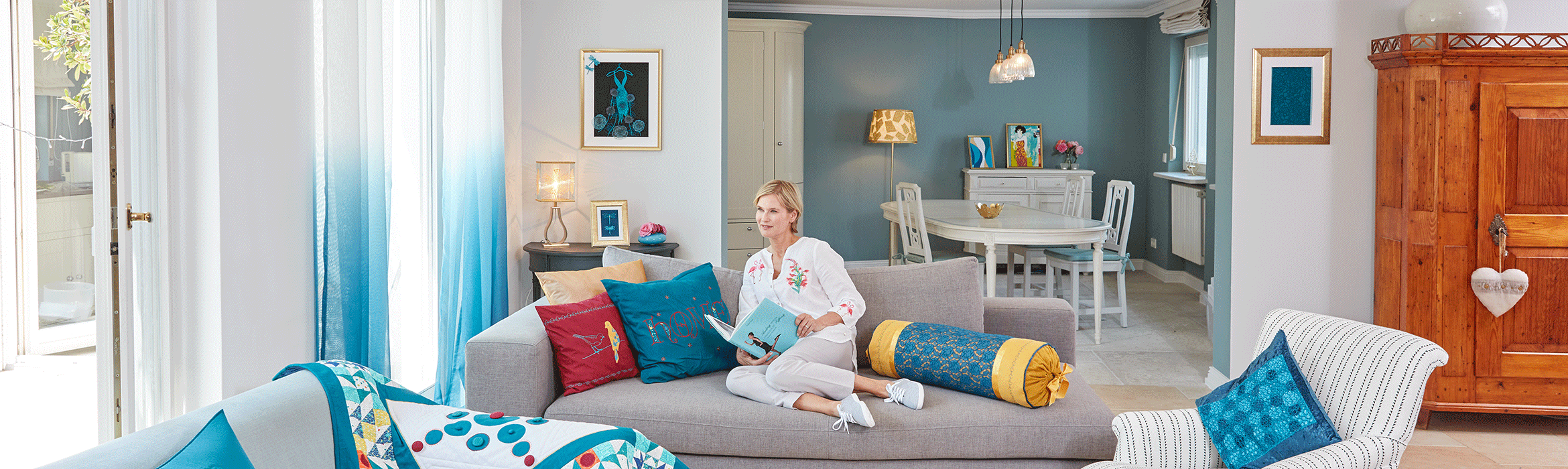 Living room with quilt, embroidered pillows and lady reading book