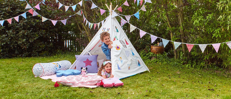 Mädchen und Junge schauen aus mit Disney-Motiven besticktem Zelt