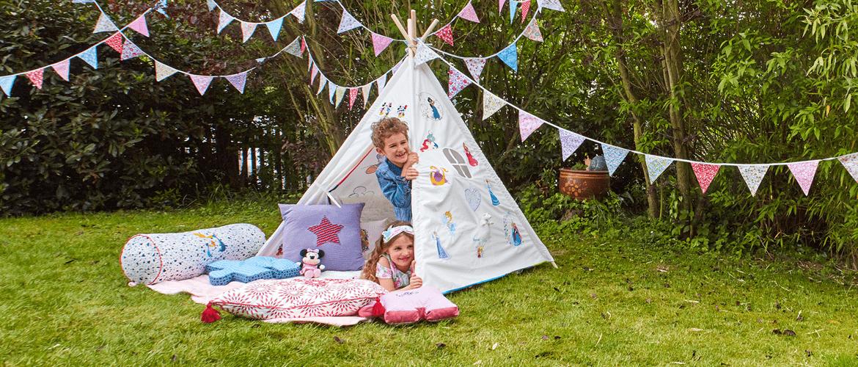 Fille et garçon sortant d'une tente brodée de motifs Disney