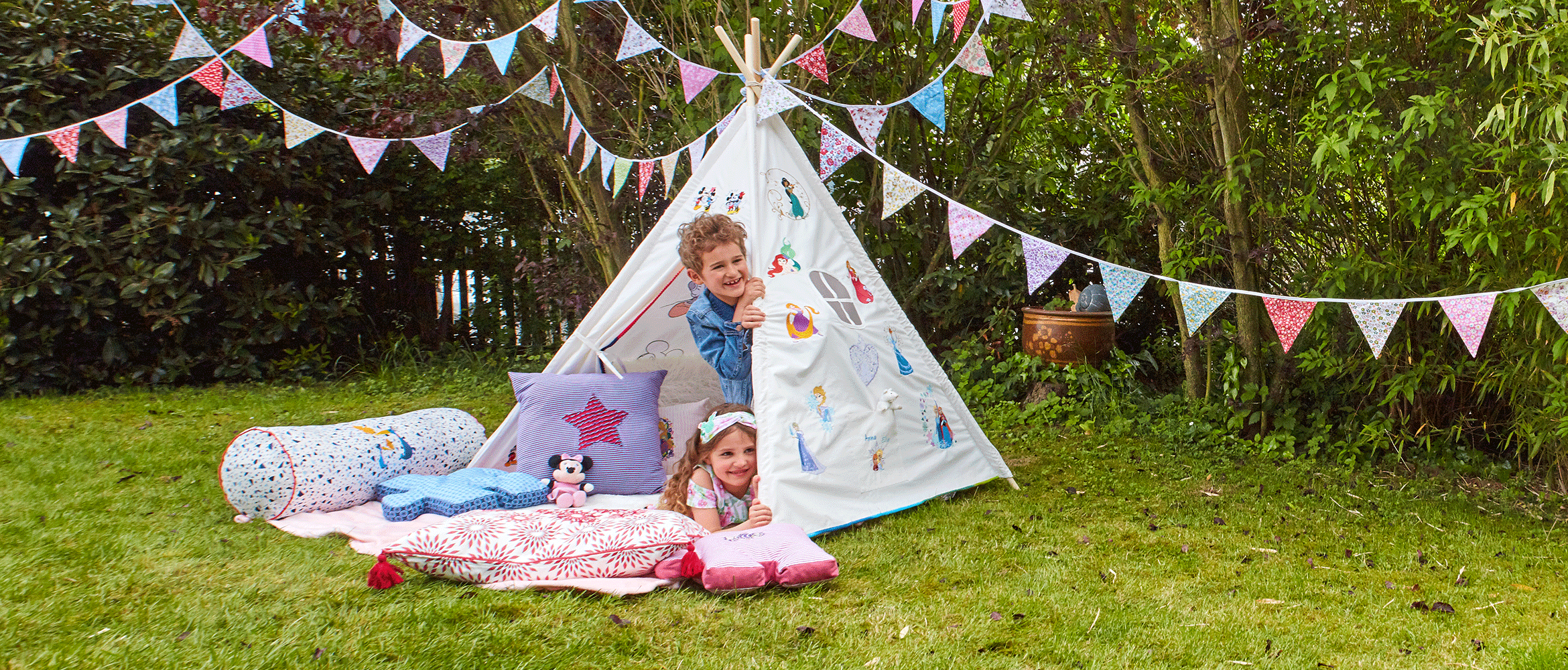 Girl and boy peaking out of tent embroidered with Disney designs