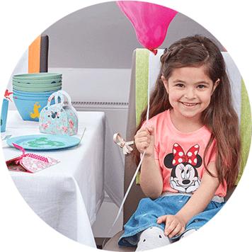 Kleines Mädchen mit rosa Ballon in orangefarbenem Minnie-Maus-T-Shirt