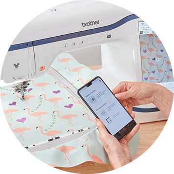 My Design Snap app on mobile in front of embroidery of flamingos